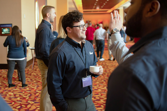 Communications Project Supervisor Aaron Hawkes Talks With A Client At The 2019 Xtend Leadership Conference.
